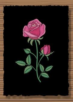 Floral genähte verzierung mit stichrose. stickereiblume auf einem dunklen klappenstoff und einem hölzernen beschaffenheitshintergrund.