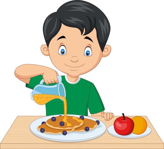 Flüssiger ahornsirup des kleinen jungen auf pfannkuchen mit blaubeeren
