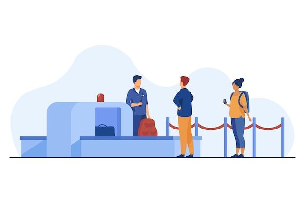 Flughafenarbeiter, der passagiergegenstände durch scanner überprüft.