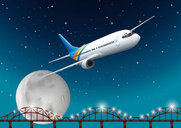 Flugzeug, das über brücke nachts fliegt