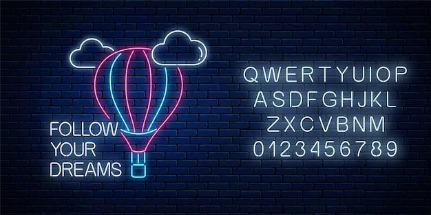 Folgen sie ihren träumen - leuchtende neon-inschriftenphrase mit heißluftballonzeichen mit alphabet auf dunkler backsteinmauer