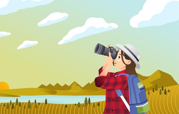 Fotograf der jungen frauen, die himmel mit sonnenuntergangansicht und schöner landschaft fotografieren