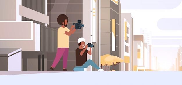 Fotograf und kameramann, der kameras verwendet, die videoaufnahmen machen, die bilder zusammenarbeiten, die über modernen stadtgebäuden außerhalb des stadtbildhintergrunds horizontal in voller länge arbeiten