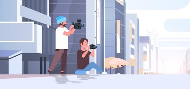 Fotograf und kameramann, der kameras verwendet, die videoaufnahmen machen, die zusammenarbeiten, die zusammen über modernen stadtgebäuden außerhalb des stadtbildhintergrunds horizontal in voller länge flach arbeiten