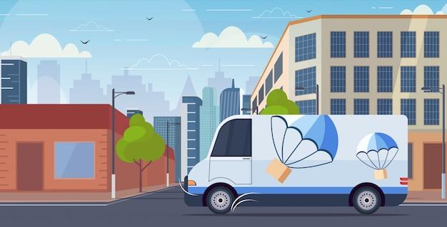 Frachtwagen-lkw, der stadtstraßen-paketbox mit fallschirm fährt, der vom himmel express-zustelldienstkonzept modernen stadtbildhintergrund horizontal herabfliegt
