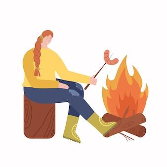 Frau brät würstchen auf dem scheiterhaufen. erholung im freien.