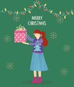 Frau der frohen weihnachten mit der hässlichen strickjacke, die geschenk hält, beleuchtet dekoration