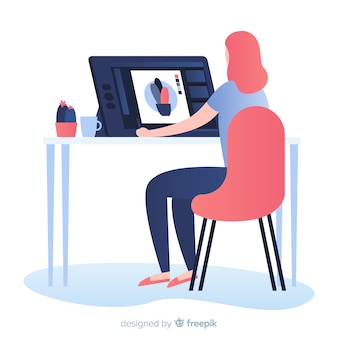Frau, die am grafikdesignerarbeitsplatz sitzt