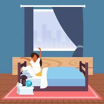 Frau, die arme streckt, die am morgen afican amerikanisches mädchen aufwachen, das auf bett nach guter nachtschlaf moderne wohnung schlafzimmer interieur sitzt