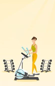 Frau, die auf elliptischem trainer trainiert.