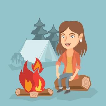 Frau, die auf klotz nahe lagerfeuer im kampieren sitzt.