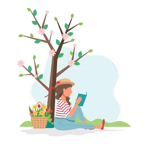 Frau, die buch unter dem baum im frühjahr liest.