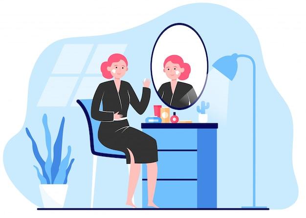Frau, die creme auf gesichtshaut am spiegel anwendet
