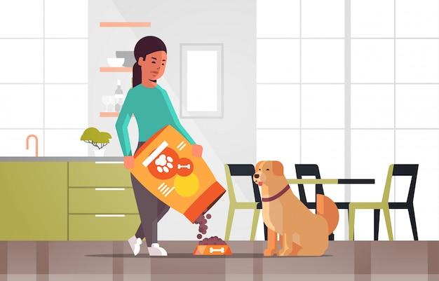 Frau, die das hungrige labrador-apportierhundmädchen gibt ihrem hund das häusliche leben der trockenfutterkörnchen mit innenhorizontalen der modernen küche des haustierkonzeptes in voller länge einzieht