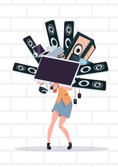 Frau, die den computer und moderne elektronik-geräte stehen über weißem backsteinmauer-cyber montag hält