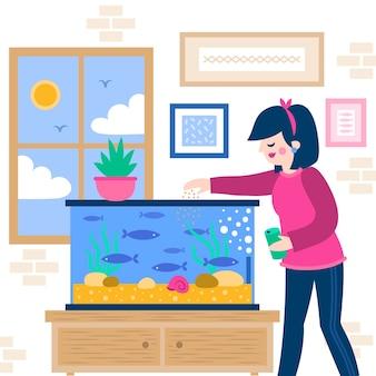 Frau, die den fisch vom aquarium füttert