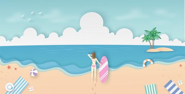 Frau, die ein surfbrett auf dem strand hält und zum meer, zur wolke und zum blauen himmel mit papierschnitt schaut