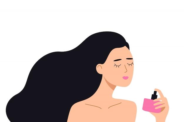 Frau, die eine flasche parfüm in der hand hält, genießt das aroma von toilettenwasser.