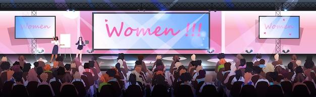 Frau, die eine präsentation vor dem publikum von mädchen des bühnenfrauenclubs hält, die sich gegenseitig beim konzept der vereinigung der feministinnen unterstützen