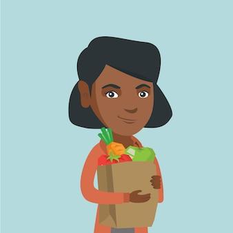 Frau, die einkaufstasche mit gesundem lebensmittel hält.