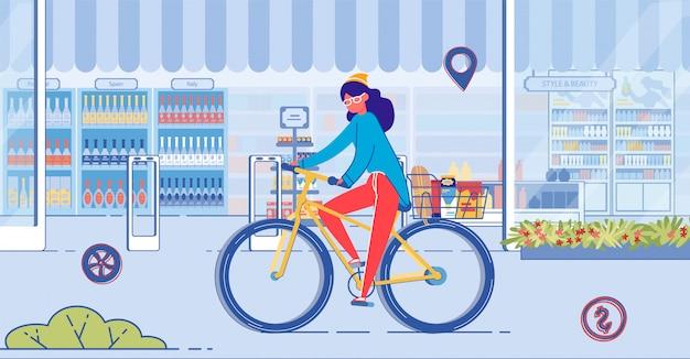 Frau, die fahrrad auf straße mit schaufenster reitet