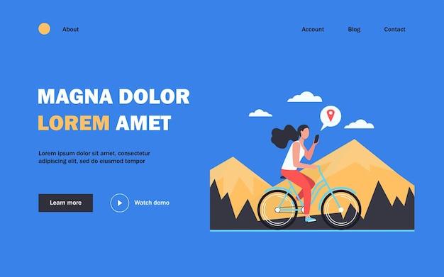 Frau, die fahrrad durch berge reitet. fahrrad- und beratungsstandort-app für mädchen auf dem handy