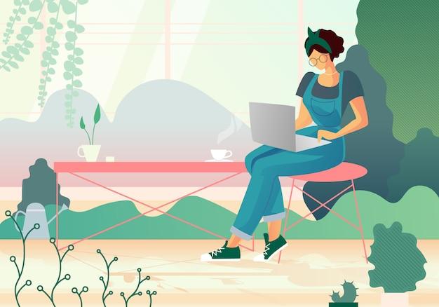 Frau, die film auf laptop im gewächshaus aufpasst. hobby