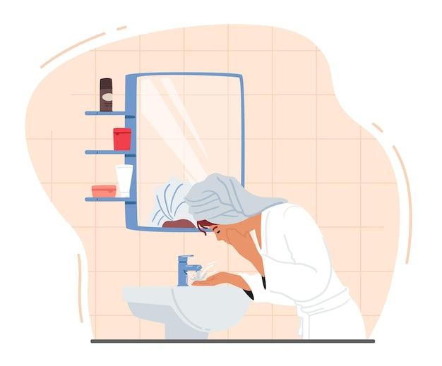 Frau, die gesicht wäscht, steht vor spiegel und waschbecken im badezimmer. mädchen in handtuch und bademantel, das hautpflegeverfahren anwendet