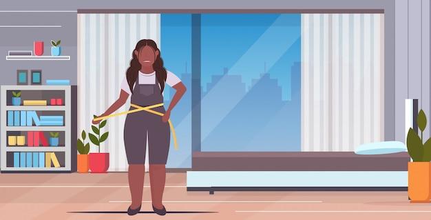 Frau, die ihre taille afroamerikaner übergewichtiges mädchen mit maßband gewichtsverlust konzept modernen schlafzimmer interieur in voller länge horizontal misst