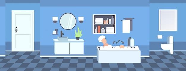 Frau, die im bad mit schaum modernes badezimmerinnenwaschbecken-tischspiegelspiegel toilette und badewannenmöbel horizontal wäscht