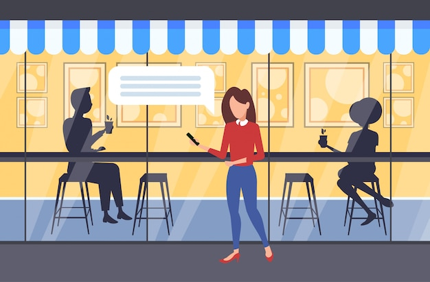Frau, die im freien unter verwendung der mobilen app-chat-blase soziale medienkommunikations-sprachkonversationskonzeptpaar-silhouette sitzt, die am tisch sitzt und kaffee modernes straßencafé außen in voller länge trinkt