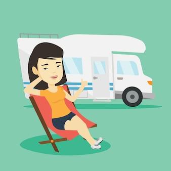 Frau, die im stuhl vor wohnmobil sitzt.