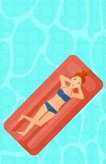Frau, die im swimmingpool sich entspannt.