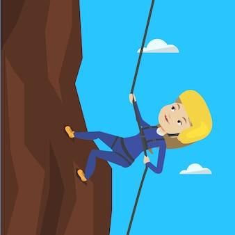 Frau, die in den bergen mit seil klettert.