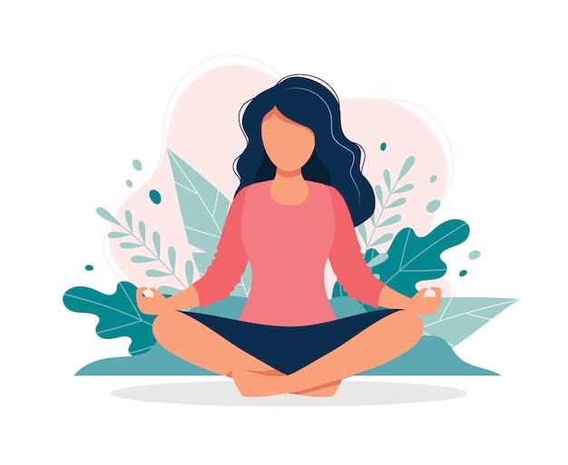 Frau, die in der natur und in den blättern meditiert.