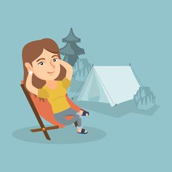 Frau, die in einem klappstuhl im kampieren sitzt.