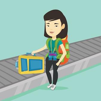 Frau, die koffer auf gepäckförderband aufnimmt