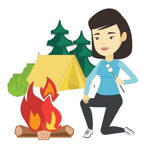Frau, die marshmallow über lagerfeuer röstet.