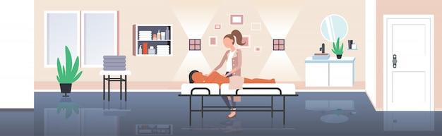 Frau, die masseurin der körperformung erhält, macht anti-cellulite-entspannungsverfahren hautpflege-massagetherapiekonzept des modernen spa-saloninnenraums horizontal in voller länge