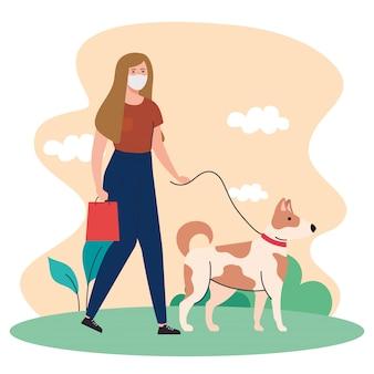 Frau, die medizinische maske trägt, die mit haustierhund an der leine im freien geht