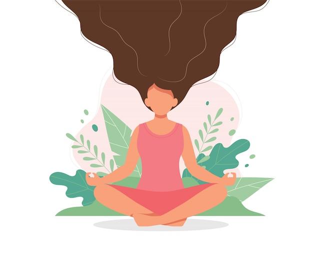 Frau, die mit blättern und ihrem haar oben meditiert.