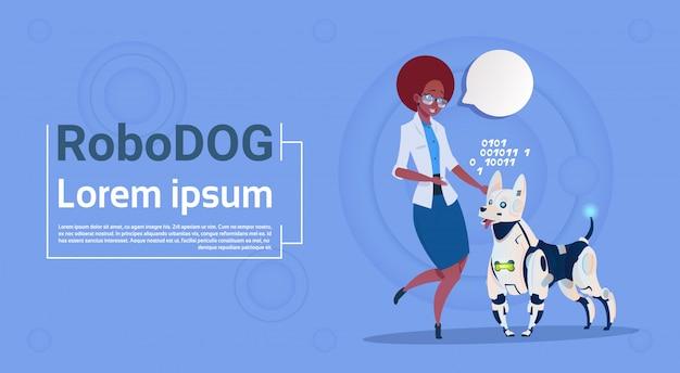 Frau, die mit roboterhund-netter haustier-moderner roboter-haustier-künstlicher intelligenz-technologie spielt
