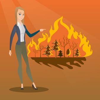 Frau, die nahe bei verheerendem feuer steht.