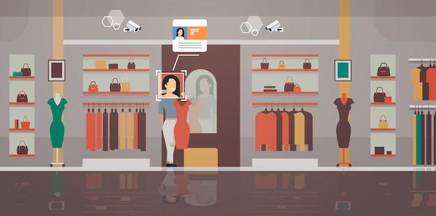 Frau, die neue kleiderbekleidungsgeschäft-kundenidentifikation-gesichtserkennung modernes boutique-innenüberwachungskameraüberwachungs-cctv-system anprobiert