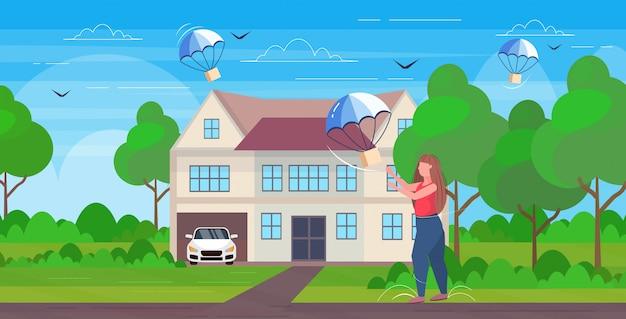 Frau, die paketbox fängt, die mit fallschirm vom himmel transporttransportpaket luftpost expressversandkonzept cottage haus landschaft hintergrund voller länge horizontal herunterfällt