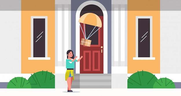 Frau, die paketbox fängt, die mit fallschirm vom himmeltransport-versandpaket herunterfällt luftpost expresspostversandkonzept modernes hausgebäude außen in voller länge flach horizontal
