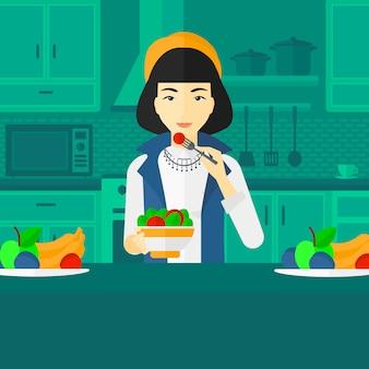 Frau, die salat isst.