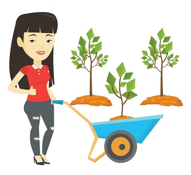 Frau, die schubkarre mit pflanze drückt.