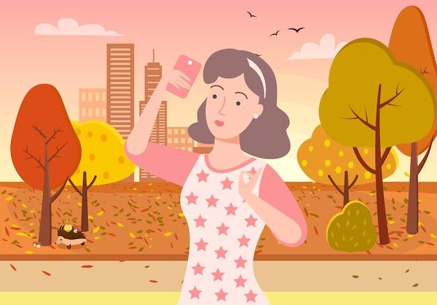 Frau, die selfie in autumn park am telefon nimmt