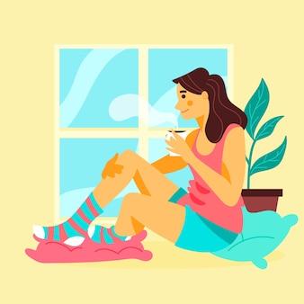 Frau, die sich zu hause mit einem tasse kaffee entspannt